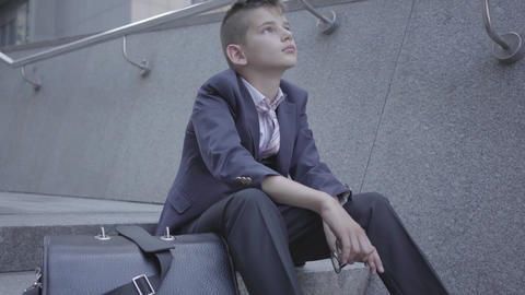 Sad well-dressed boy sitting on the stairs on the street. The boy is tired and Footage