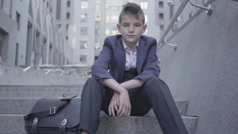 Pensive well-dressed cute boy sitting on the stairs on the street. The boy is Live Action
