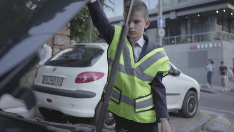 Confident little boy wearing safety equipment standing by the open hood of a Footage