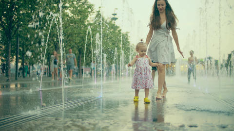 Mom and her little baby having fun while walking in the fountain, slow motion Footage