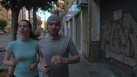 A young couple jogging on a paved sidewalk Footage