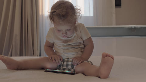 A baby girl in checkered shorts sitting on a bed with a tablet in front of her Live Action