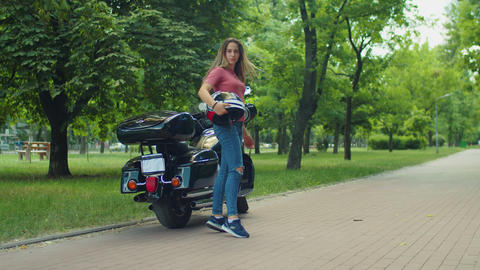 Cute biker girl with helmet posing by motorcycle Live Action