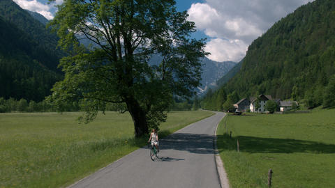 Aerial - Flying in front of a woman in white dress riding bicycle on rural road Footage