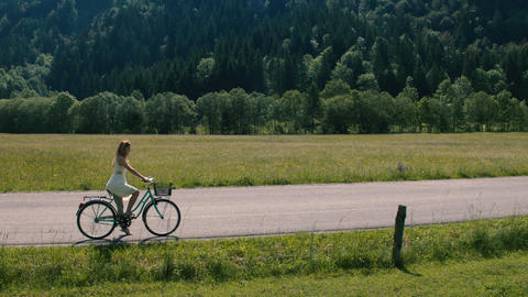Aerial - Young woman in a white dress riding bicycle on a rural road Footage
