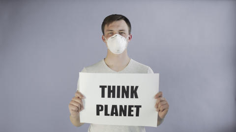 Young Man Activist With mask on face and with Think Planet Poster on grey Live Action