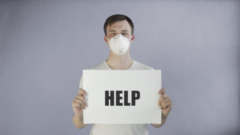 Young Man Activist With mask on face and with HELP Poster on grey background Live Action