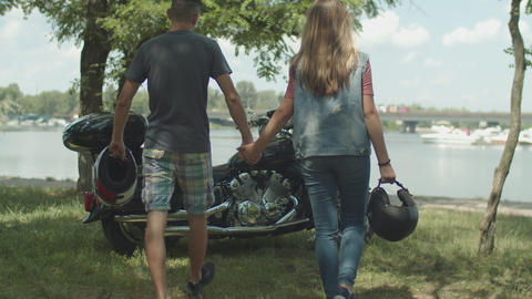 Motorcycle couple holding helmets in hands walking Live Action