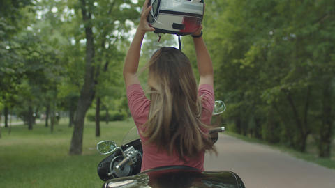 Pretty blond girl enjoying motorbike ride outdoor Footage