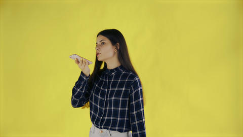 Beautiful brunette woman records a voice message on her mobile phone on yellow Live Action