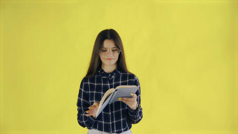 Beautifu young girl in glasses is reading book isolated on yellow background Archivo