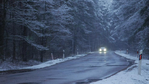 The car moves on a snowy forest road at dusk. Winter season Footage