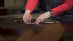 master marks the treated animal skin. He applies and tracks a cardboard template Footage