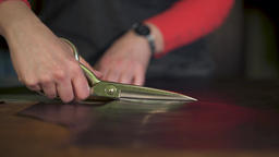 Women hands Cutting scissors cut the skin on the table, making leather goods Footage