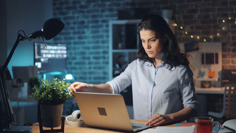 Girl leaving workplace at night turning off laptop and lamp and going away Footage