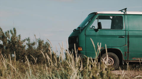 Old rusty green minivan parked on dirty road, dry grass Live Action