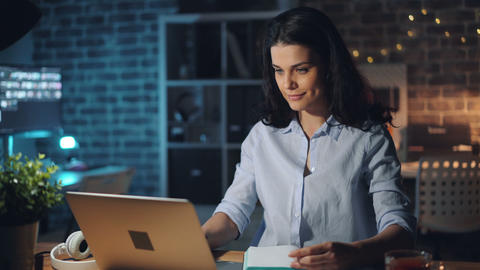 Pretty girl working with laptop at night in office smiling writing in notebook Footage