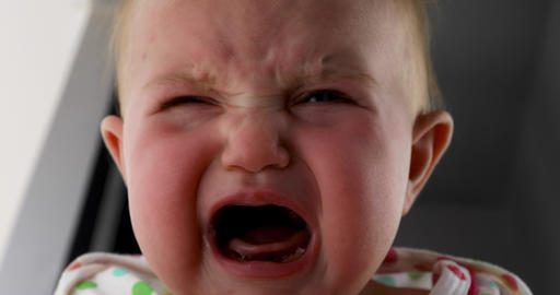 Baby crying. Indoor shot with sun light on the child face Footage