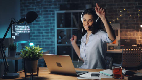 Cheerful worker listening to music dancing working with laptop in dark room Footage