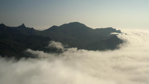 Shooting from air. Dense white cloud in foreground. Cloud huge mass covered on mountain peak. Footage