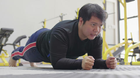 Asian fat man trying to exercise with planking in fitness gym, Healthy lifestyle, weight loss desire Live Action