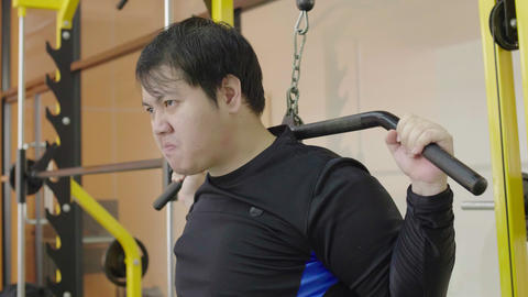 Asian fat man trying to exercise in fitness gym, Healthy lifestyle, weight loss desire, lifts heavy Live Action