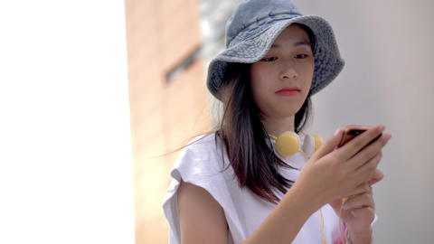 Attractive young Asian woman listening to music in headphone use smartphone, Smile portrait close up Footage
