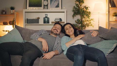Joyful couple watching TV at night laughing having fun talking at home Footage