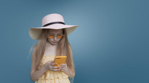 Child girl in beach style with long hair is browsing phone on blue background Footage