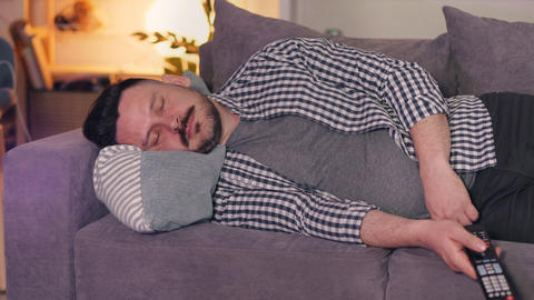 Portrait of guy in casual chothes sleeping on couch at home holding TV remote Footage