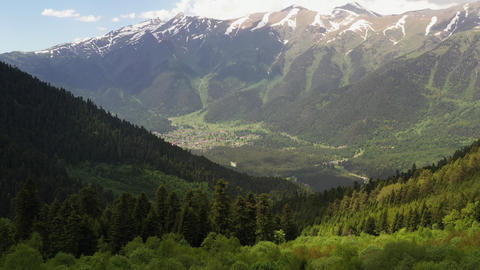 Top aerial view from pine forested hill to mountain valley. Mountain village located in beautiful Live Action