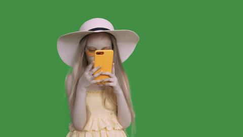 Pre-teen girl in summer hat and dress is browsing phone and thinking, alpha Footage