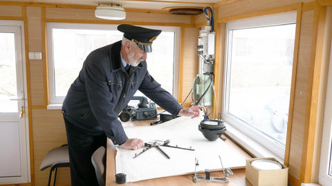 Captain of the ship is plotting the navigation route on the map in the Footage