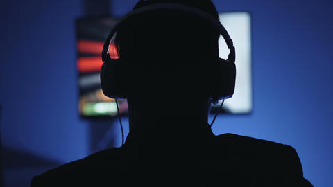 Silhouette of man in headphones playing interesting video game at home at night Footage