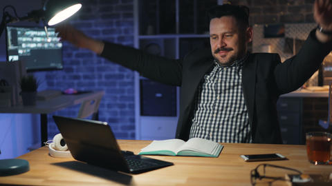 Succesful businessman working with laptop in office at night relaxing smiling Footage