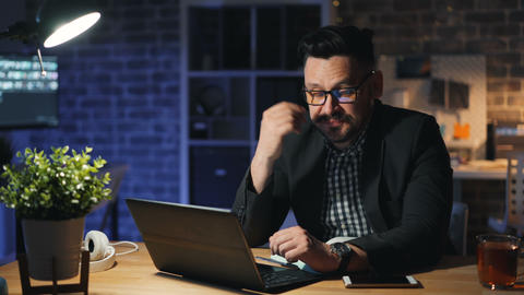 Portrait of tired office worker using laptop yawning working in office at night Live Action
