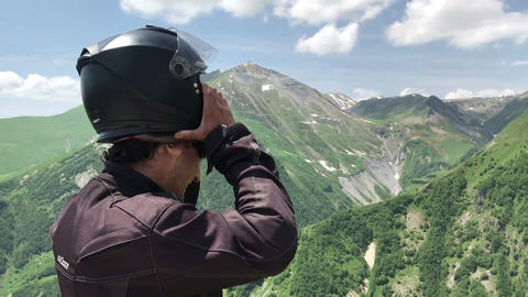 Man tourist putting of motorcycle helmet and looking around on point view in Live Action