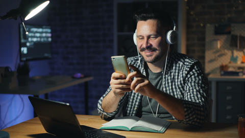 Attractive guy using smartphone and listening to music in office at night Footage