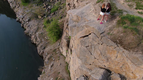Top view of two women standing on top of a high rocky cliff near a river, 4k Live Action