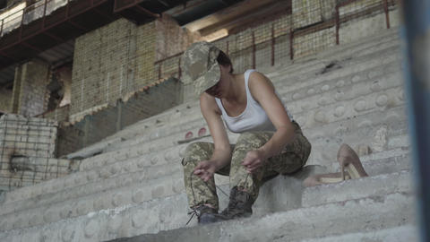 Confidient young woman in military uniform sitting on the cold concrete stairs Footage