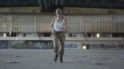 Confident young woman in military uniform training in dusty dirty abandoned Live Action