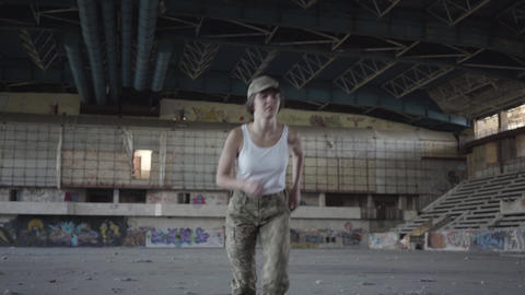 Professional young woman in military uniform training in dusty dirty abandoned Live Action