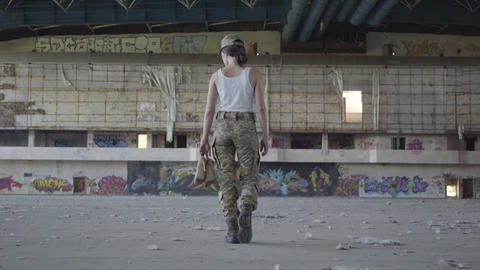 Attractive young woman in military uniform walking slowly in dusty dirty Footage