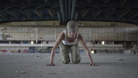 Cute strong confident young woman in military uniform push-ups in a deserted Live Action