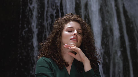 pretty young woman with curly hair enjoying the freshness of a waterfall Live Action