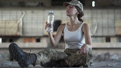 Attractive young woman in military uniform drinking water from the bottle Footage