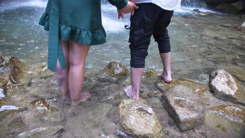 female and male bare feet from the foot just above the knees in the clear water Footage
