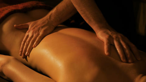 Masseur doing back massage for female client in spa center Footage