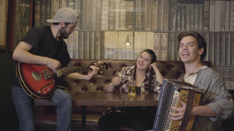 Young smiling bearded man playing guitar in the bar, his friend playing Footage