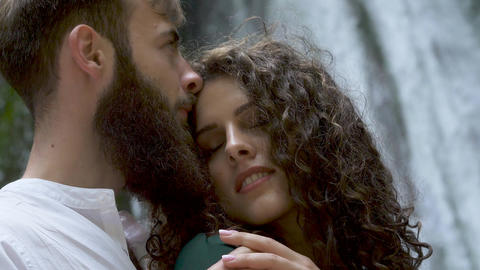 attractive man with a beard hugging a woman with curly hair from behind who Footage